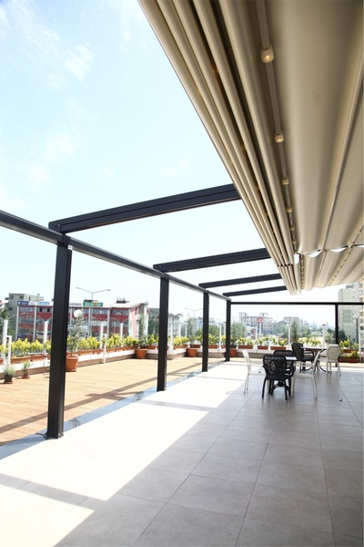 The Porolet pergola is a sleek aluminum outdoor living space with a waterproof PVC folding roof, which can be slid open partially or completely for an optimum light entrance. Unfolded it guarantees a perfect sun protection
